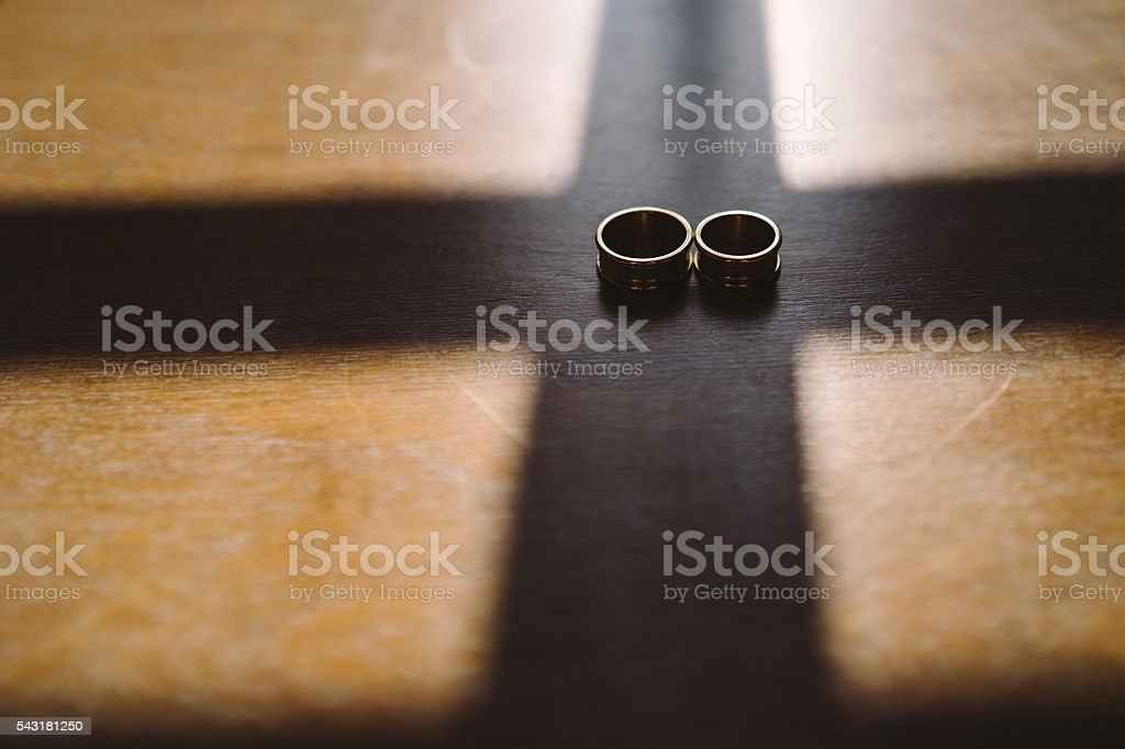 wedding rings on wooden background in sunlight and cross-shaped shadows stock photo