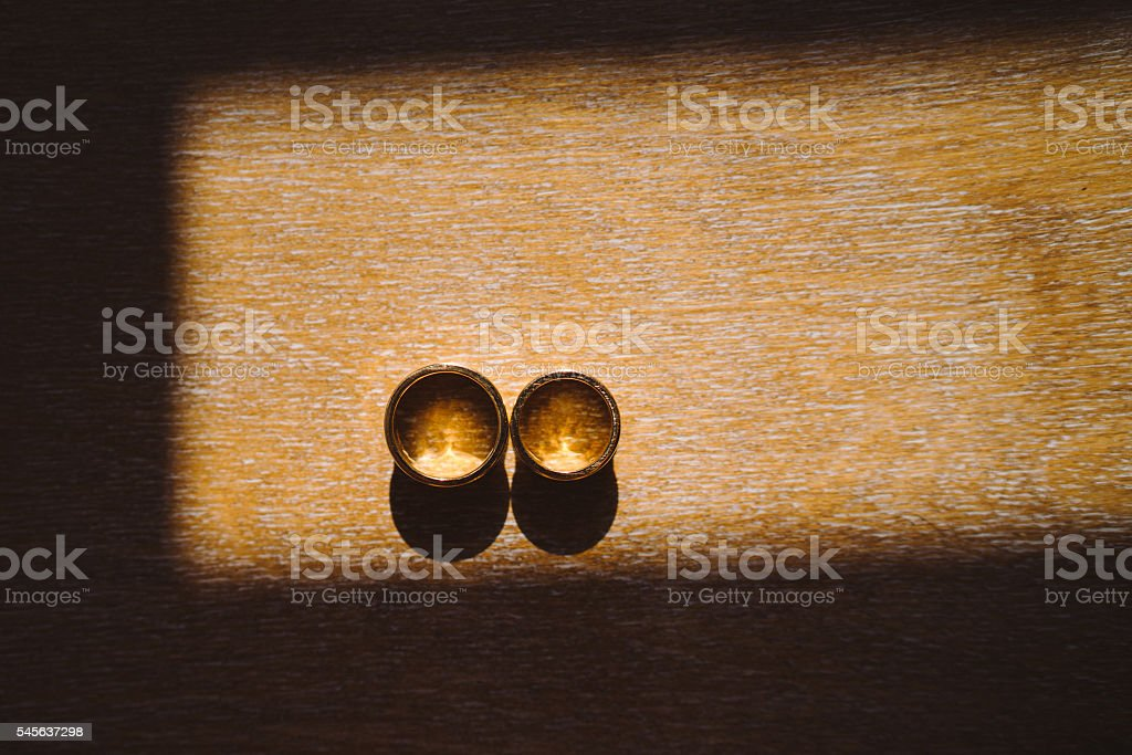 wedding rings on wooden background in sunlight stock photo
