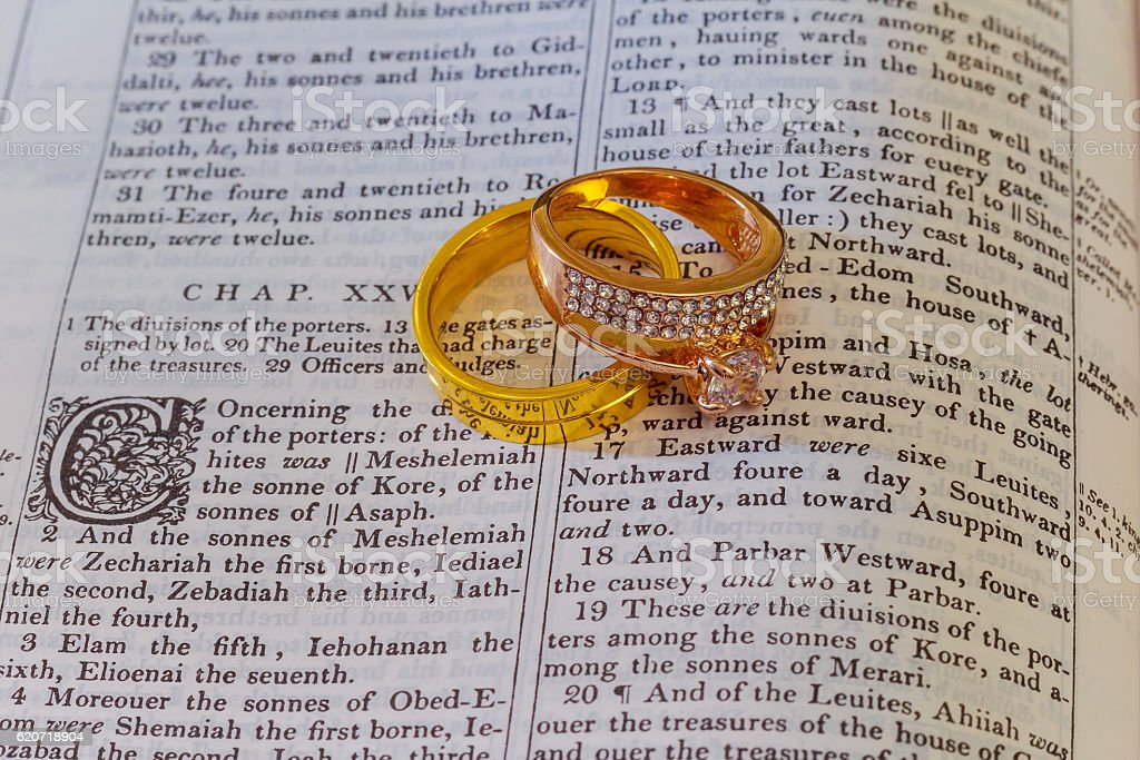 Wedding rings place on an open Bible  verse  book stock photo