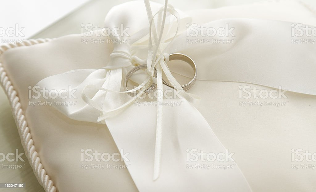 Wedding rings tied to pillow stock photo