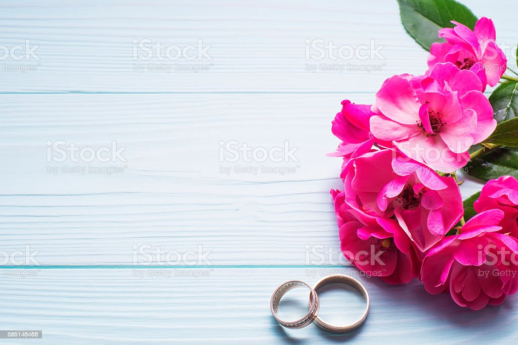 Wedding rings with pink roses on a blue wooden background. stock photo