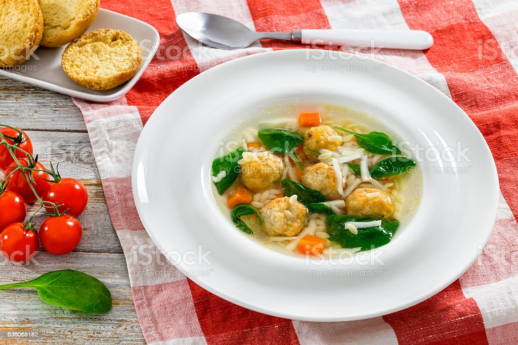 wedding soup with meatballs, small pasta risini,spinach and vege stock photo