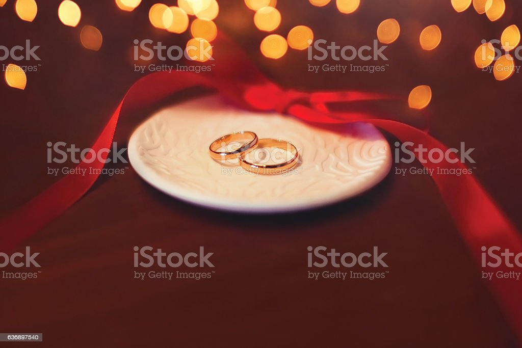 Wedding two gold rings on table with red ribbon stock photo