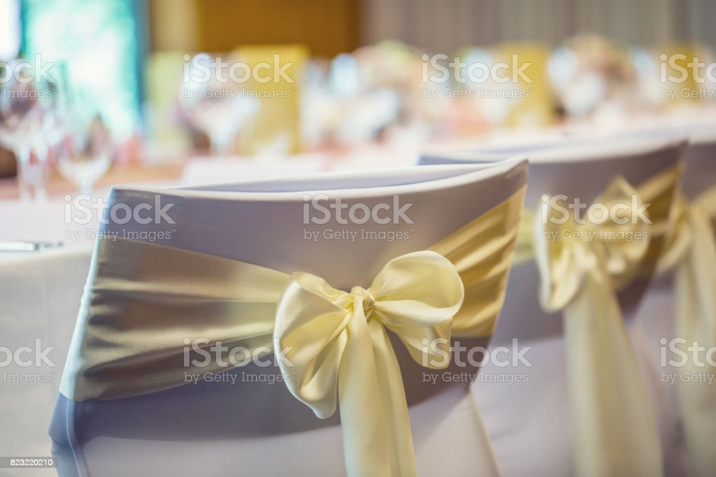 Wedding. Wedding chairs in row decorated with golden yellow color ribbon stock photo