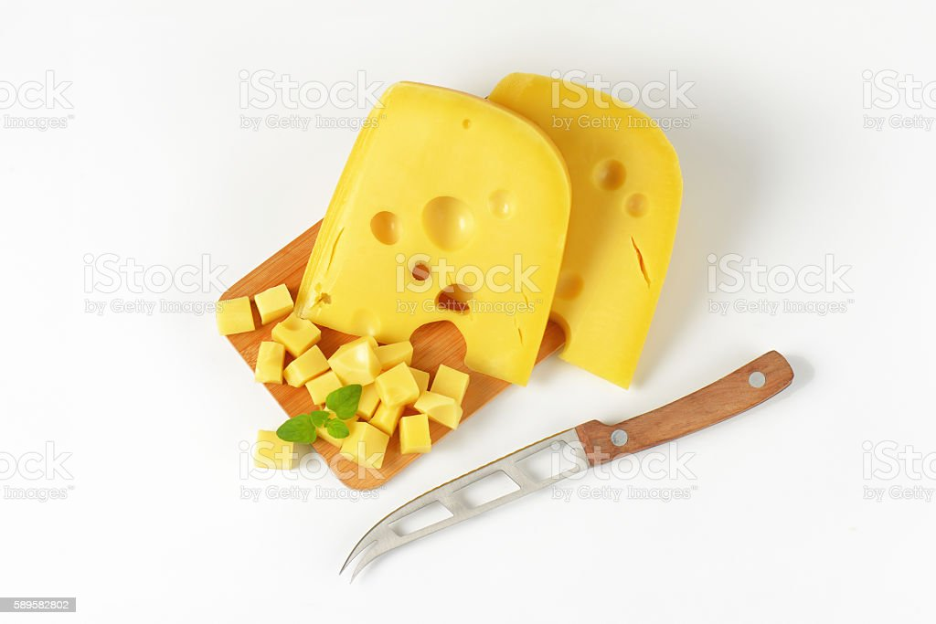 Wedges and cubes of Swiss cheese stock photo