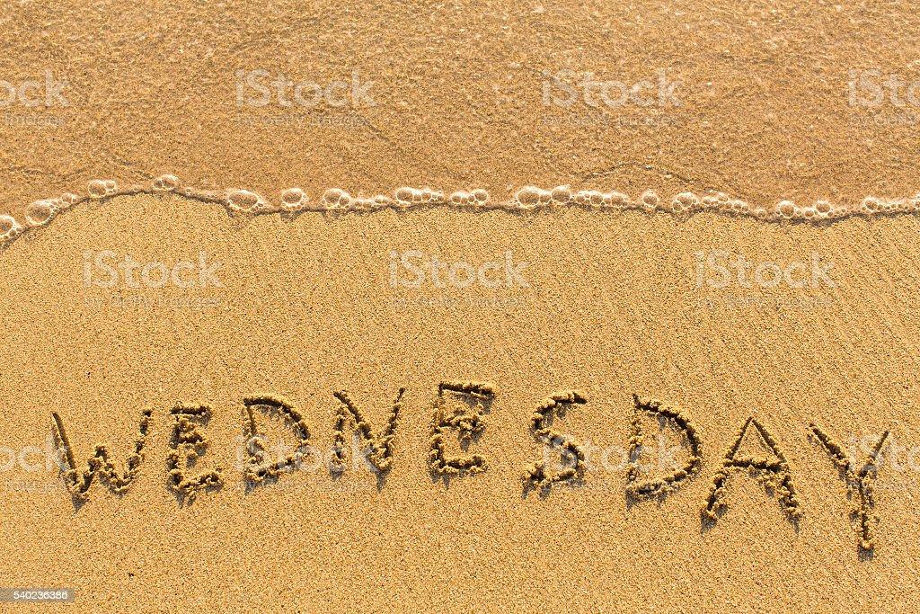 Wednesday - drawn on the sand beach stock photo