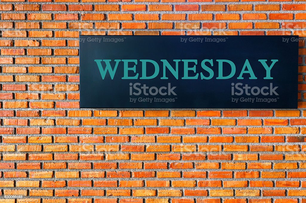 WednesDAY letters on a black background with  brick wall stock photo