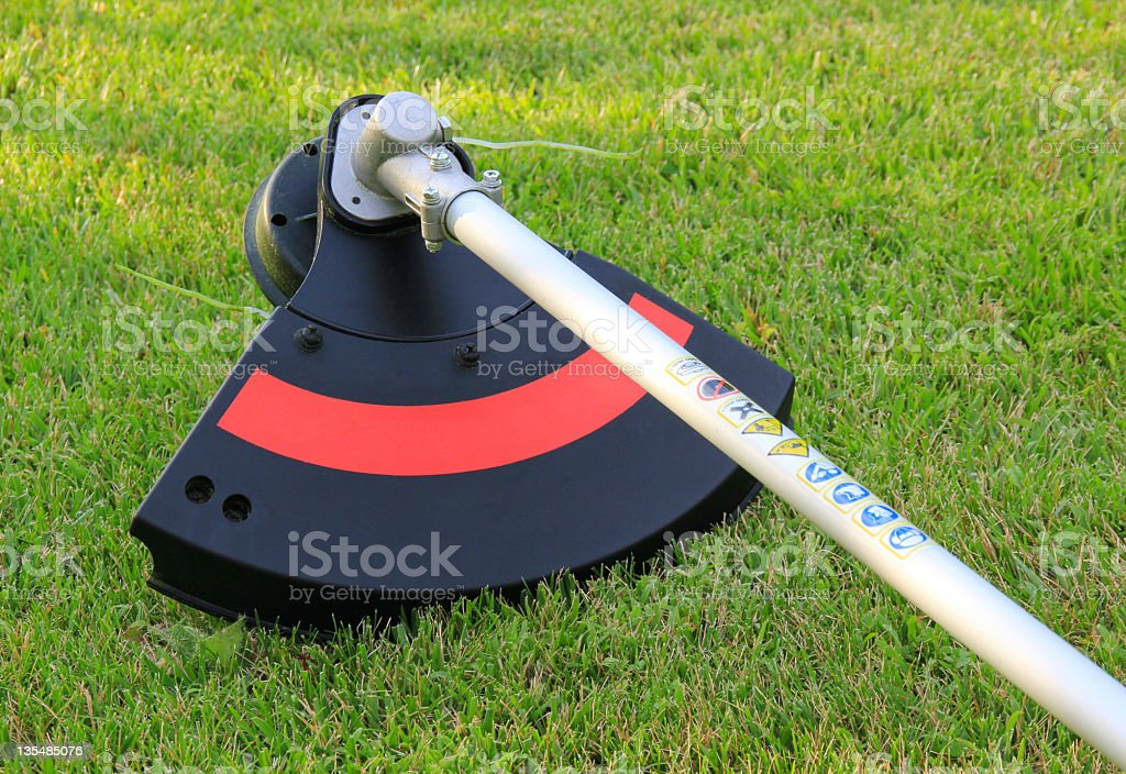 Weed trimmer in red and black on the grass stock photo