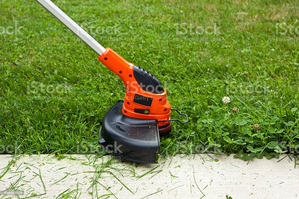 Weed Trimmer Trimming Grass Along Sidewalk stock photo