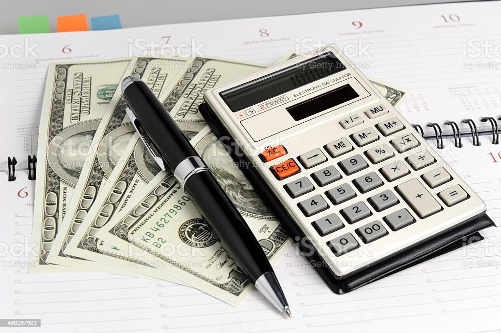 Weekly with black pen, calculator and dollars closeup stock photo