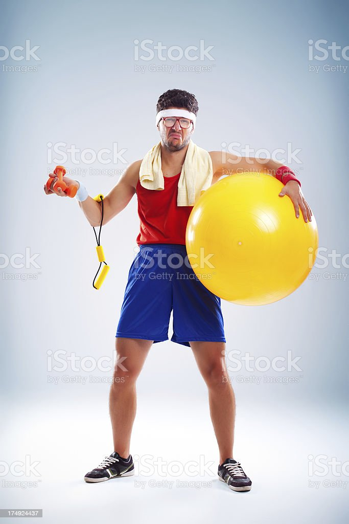 Weepy nerdy sportsman with glasses holding sporting equipment stock photo