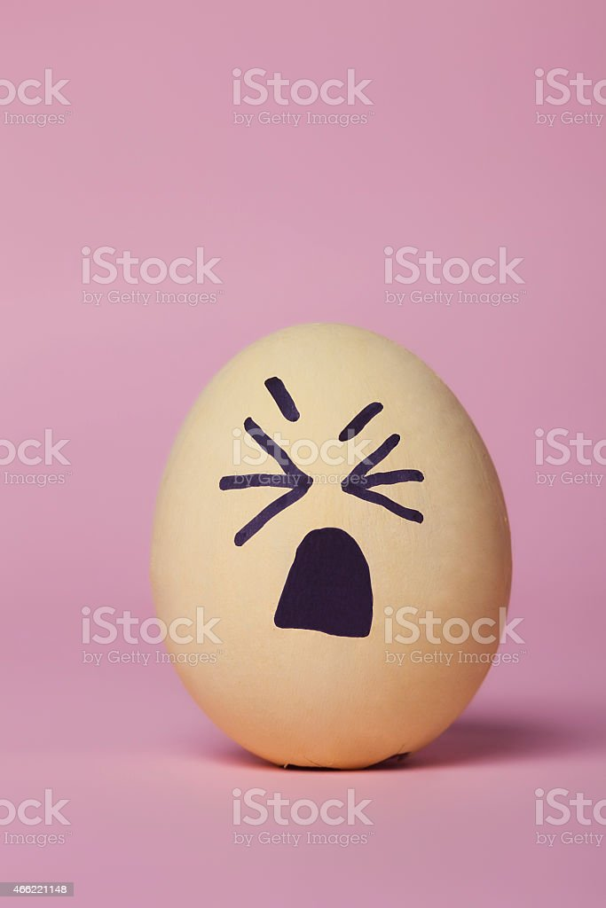 Weepy yellow painted egg vertical stock photo