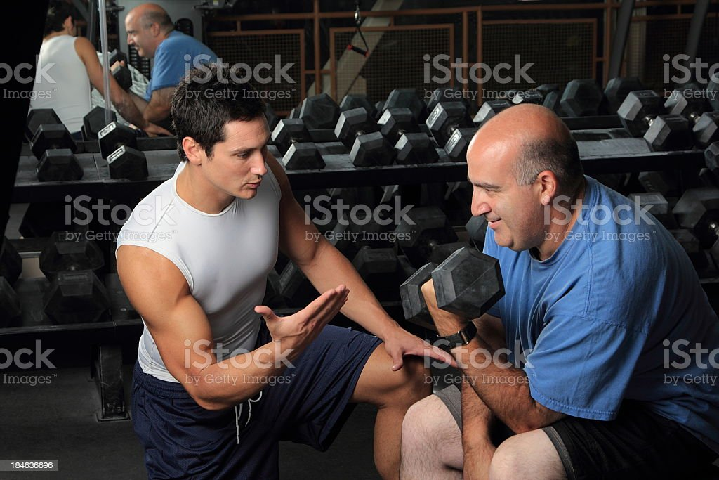 Weight lifting coach helps beginner male learn bicep curl royalty-free stock photo