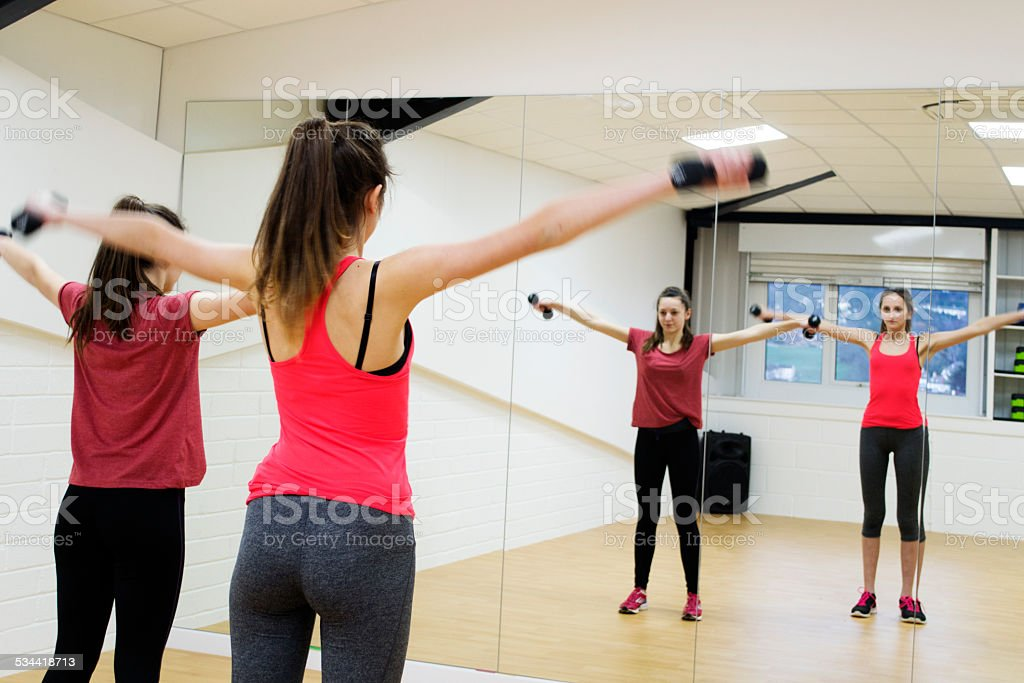 Two teenage girls working out with dumbells in a studio.