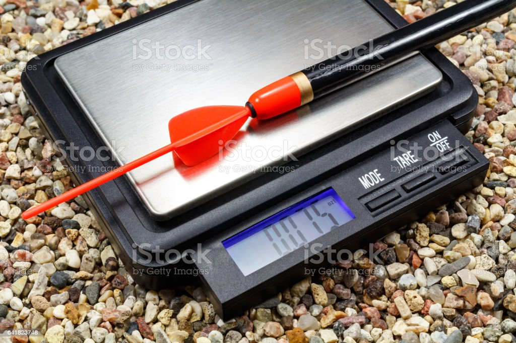 Weighting a fishing float on a pocket scale stock photo