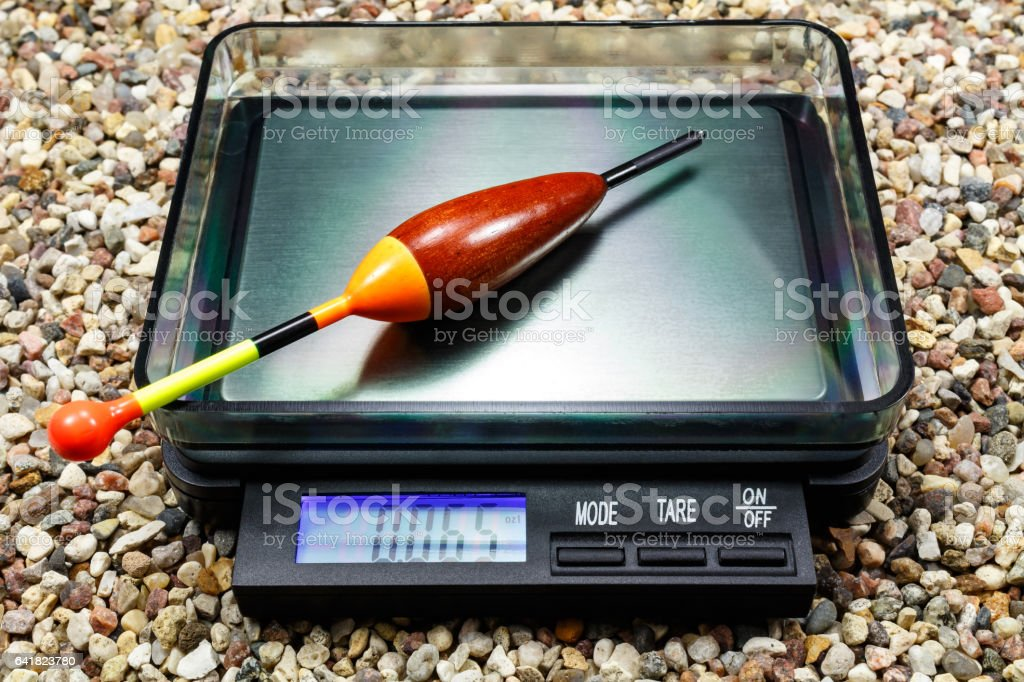Weighting a wooden fishing float on a pocket scale stock photo