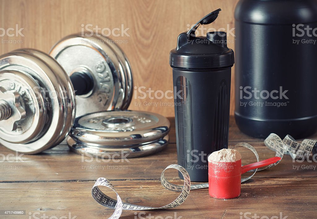 Weights, a Shake Bottle, and a Scoop of Whey Protein Powder stock photo