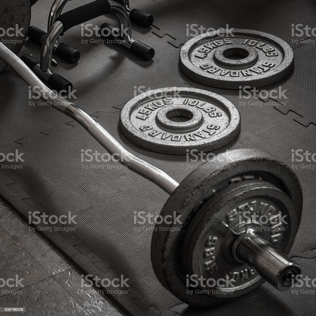 Weights and barbell on a gym mat stock photo