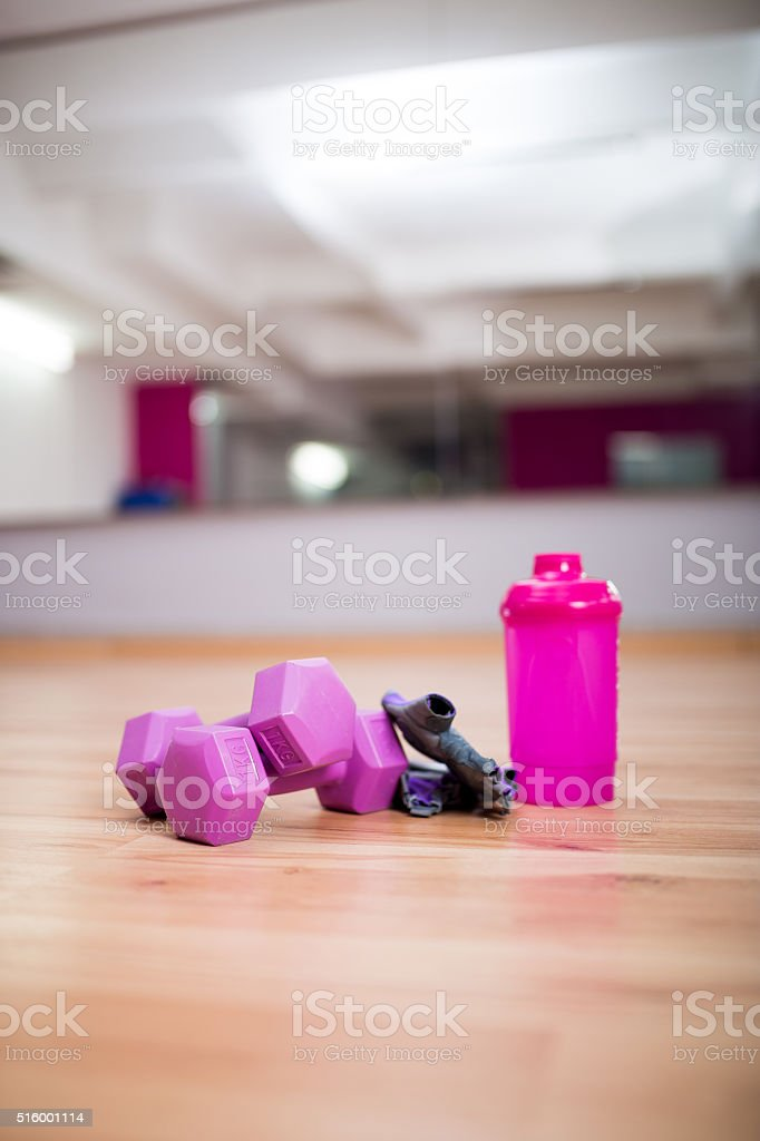 Weights,bottle of drink and protective gear at the gym stock photo