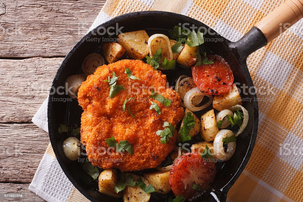 Weiner schnitzel with vegetables in a pan closeup. Horizontal stock photo