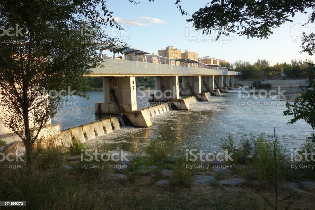 weir at the lower side from the upper part on the Ebro river behind some trees, Saragossa stock photo
