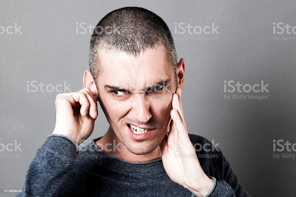 weird young man suffering from painful earache or tinnitus stock photo