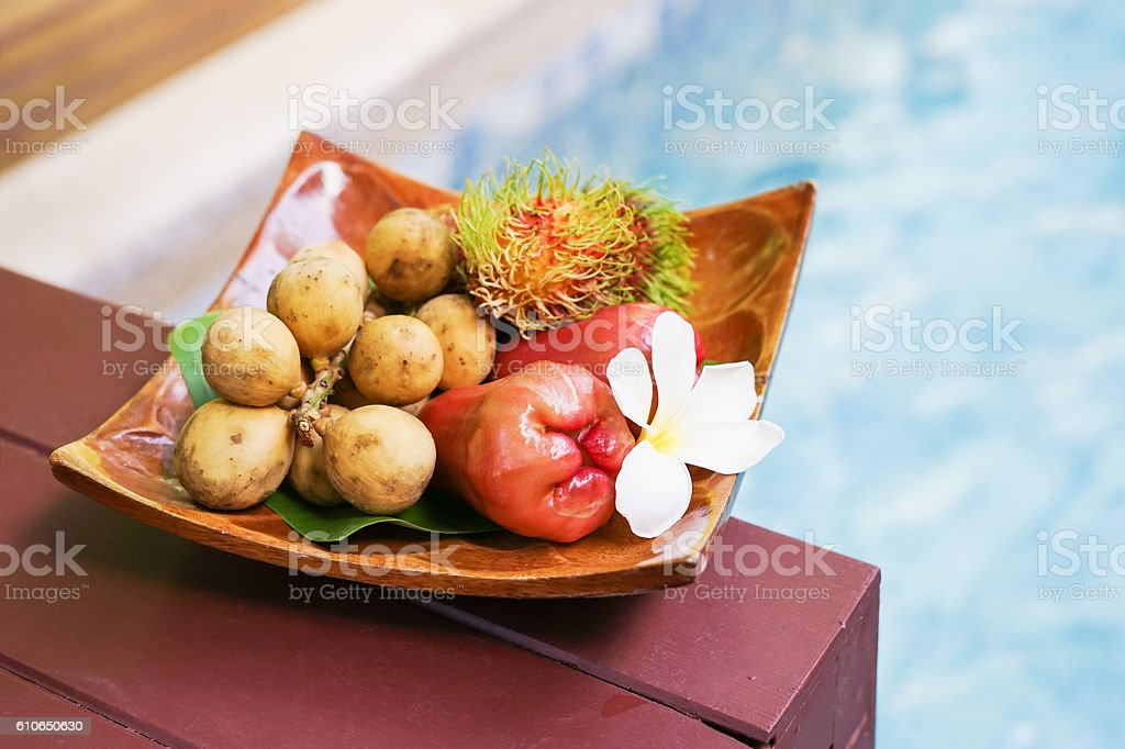 welcome fruits  on wooden tray near swimming pool stock photo