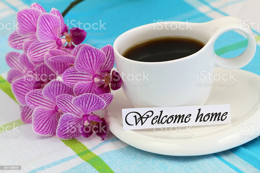 Welcome home card with cup of coffee and pink orchid stock photo
