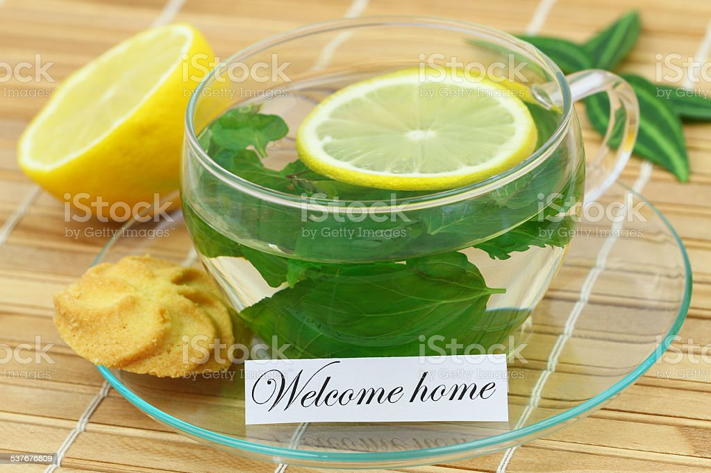 Welcome home card with cup of mint tea with lemon stock photo