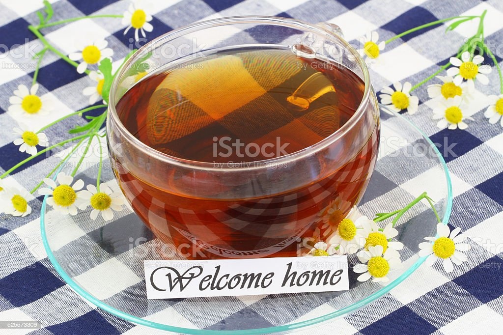 Welcome home card with cup of tea and chamomile flowers stock photo