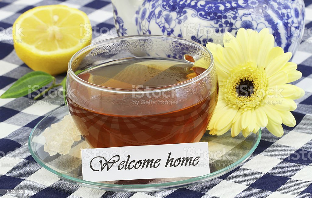 Welcome home card with cup of tea, lemon, gerbera daisy stock photo