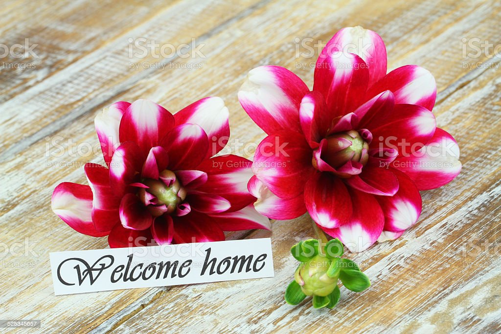 Welcome home card with dahlia flowers on rustic wooden surface stock photo