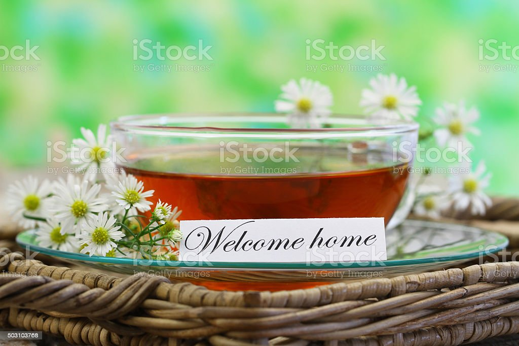 Welcome home note with cup of chamomile tea, copy space stock photo