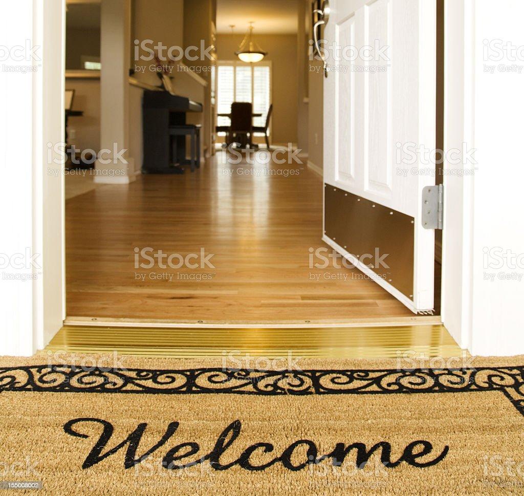 'Welcome' mat in front of white open door stock photo