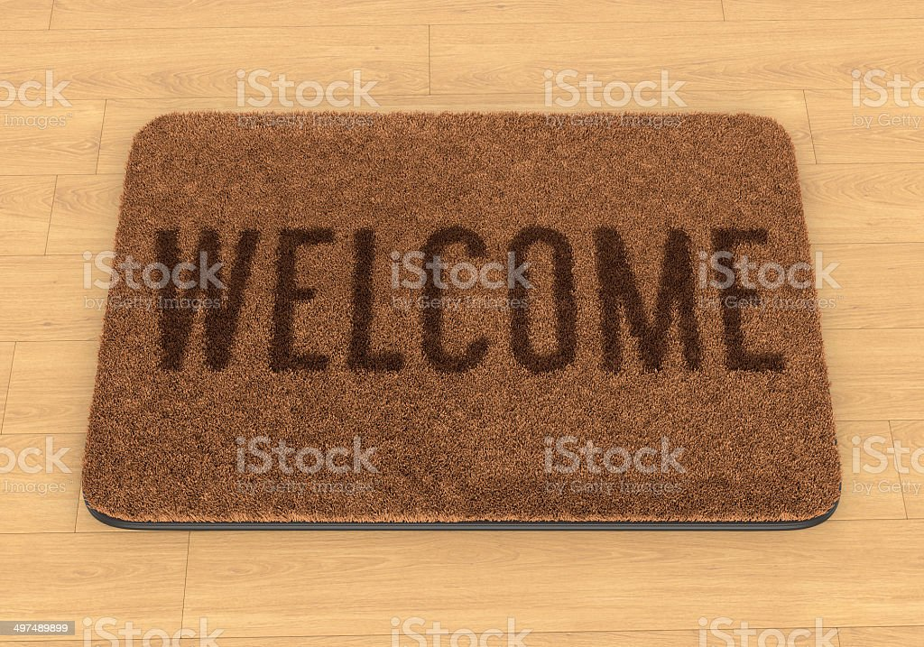 Welcome mat on wooden floor stock photo
