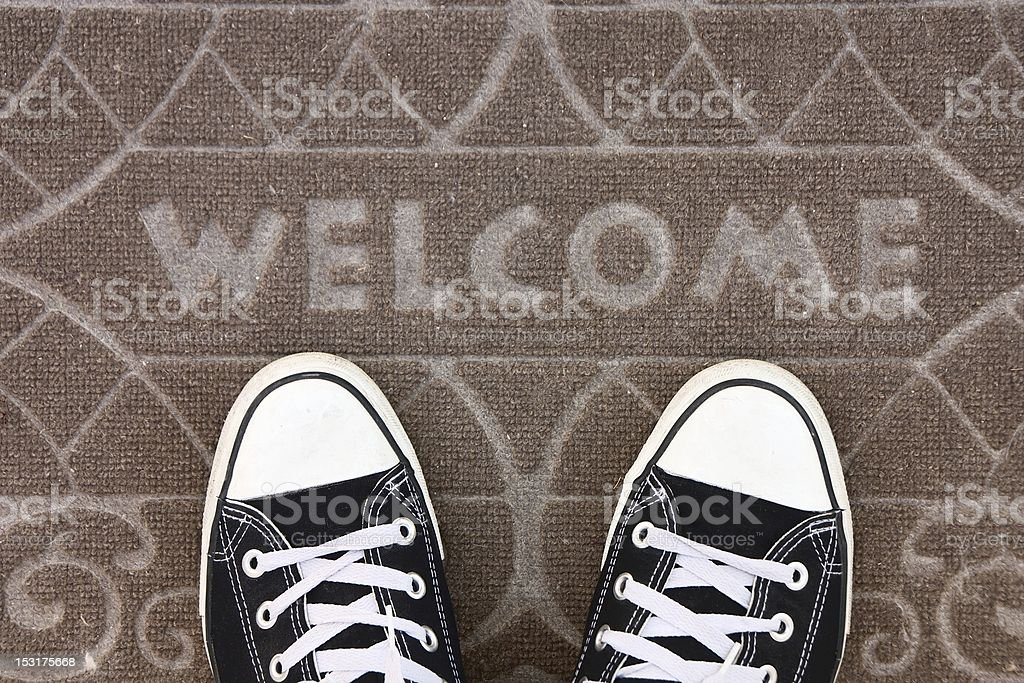 Welcome mat with black and white sneakers stock photo
