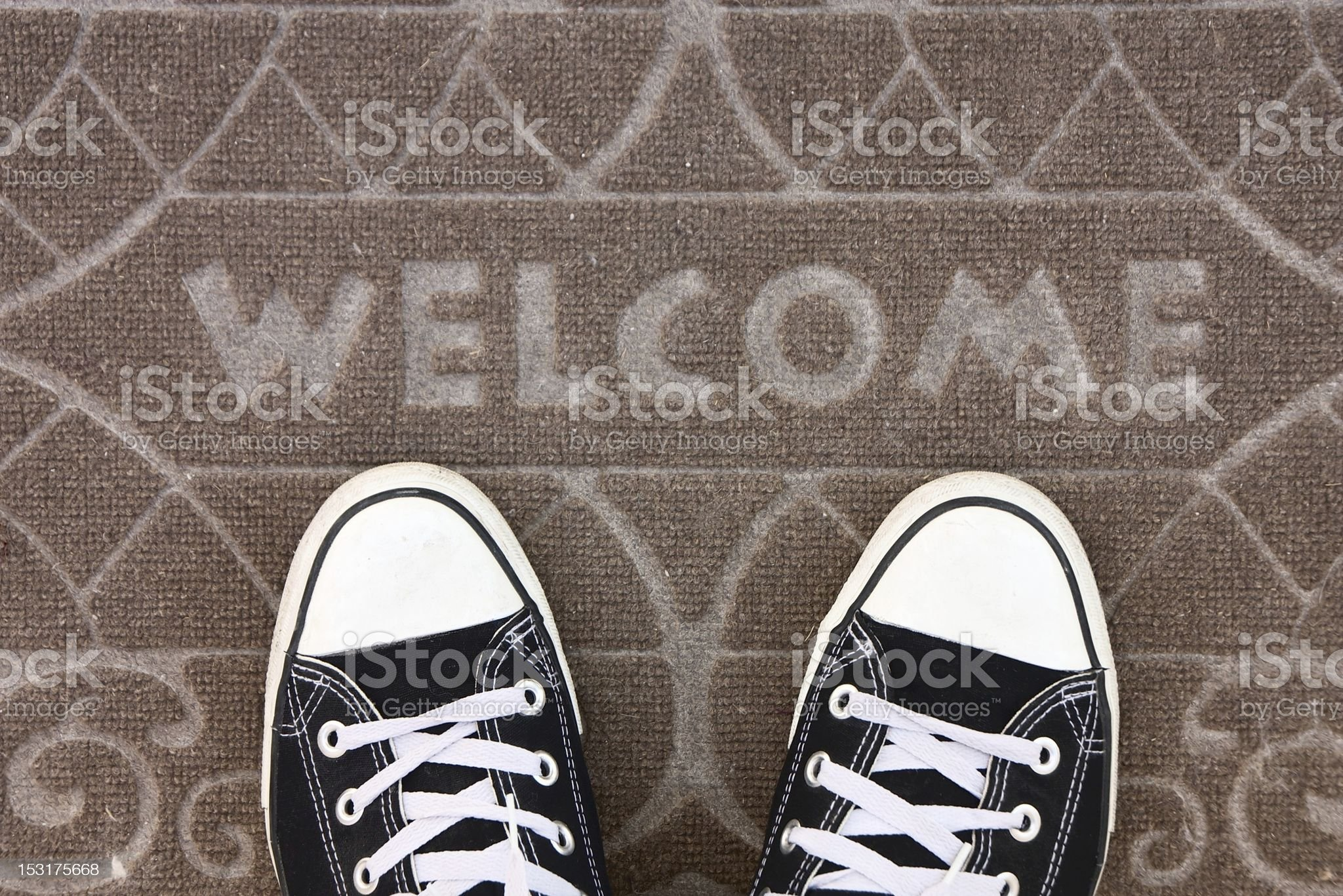 Welcome mat with black and white sneakers royalty-free stock photo