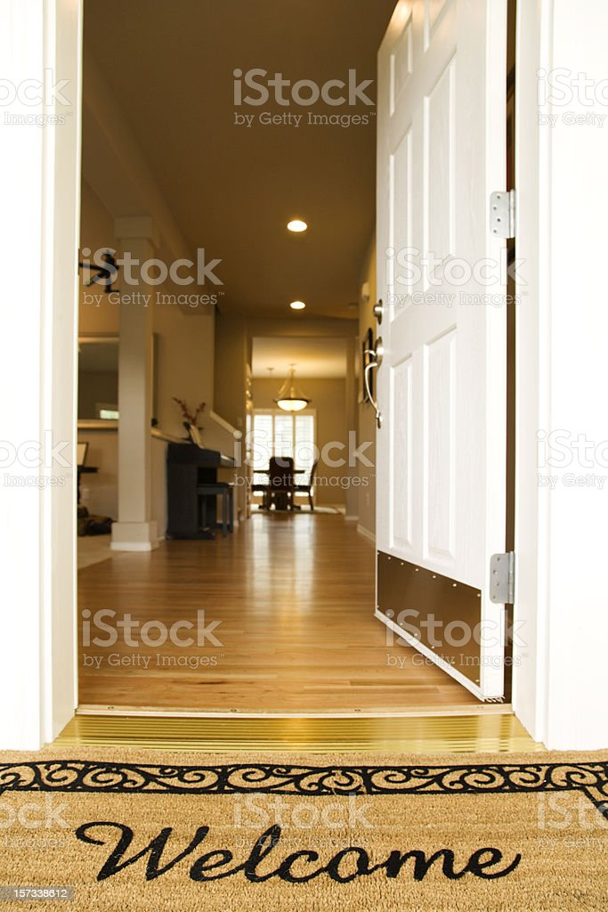 A welcome mat with the door open stock photo