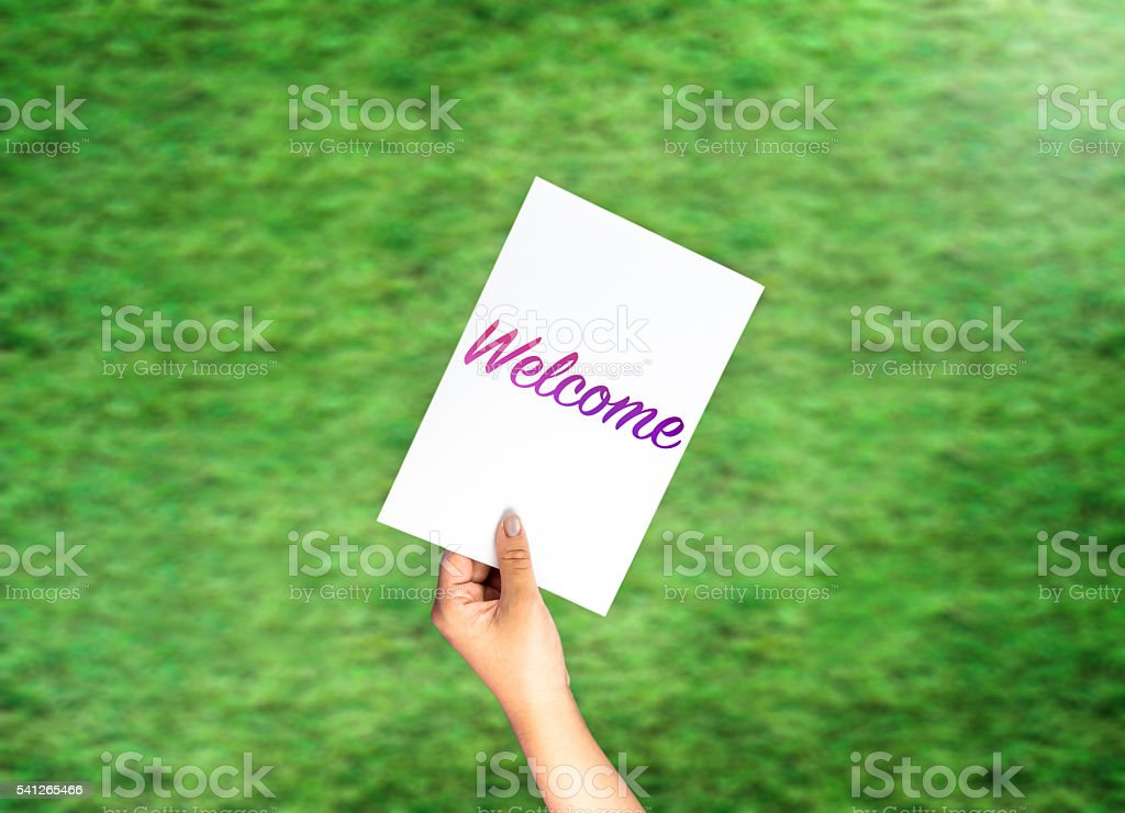 Welcome on card with hand holding on blurred grass stock photo