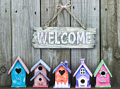Welcome sign by row of colorful birdhouses