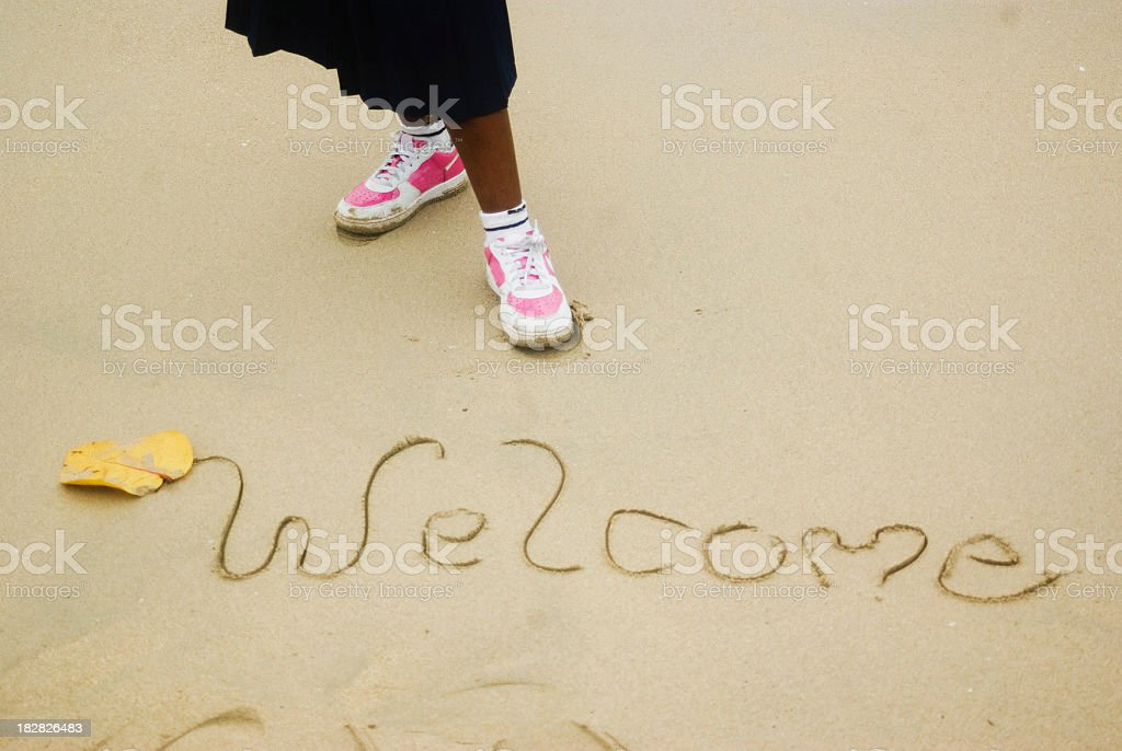 welcome sign etched in tropical sand stock photo