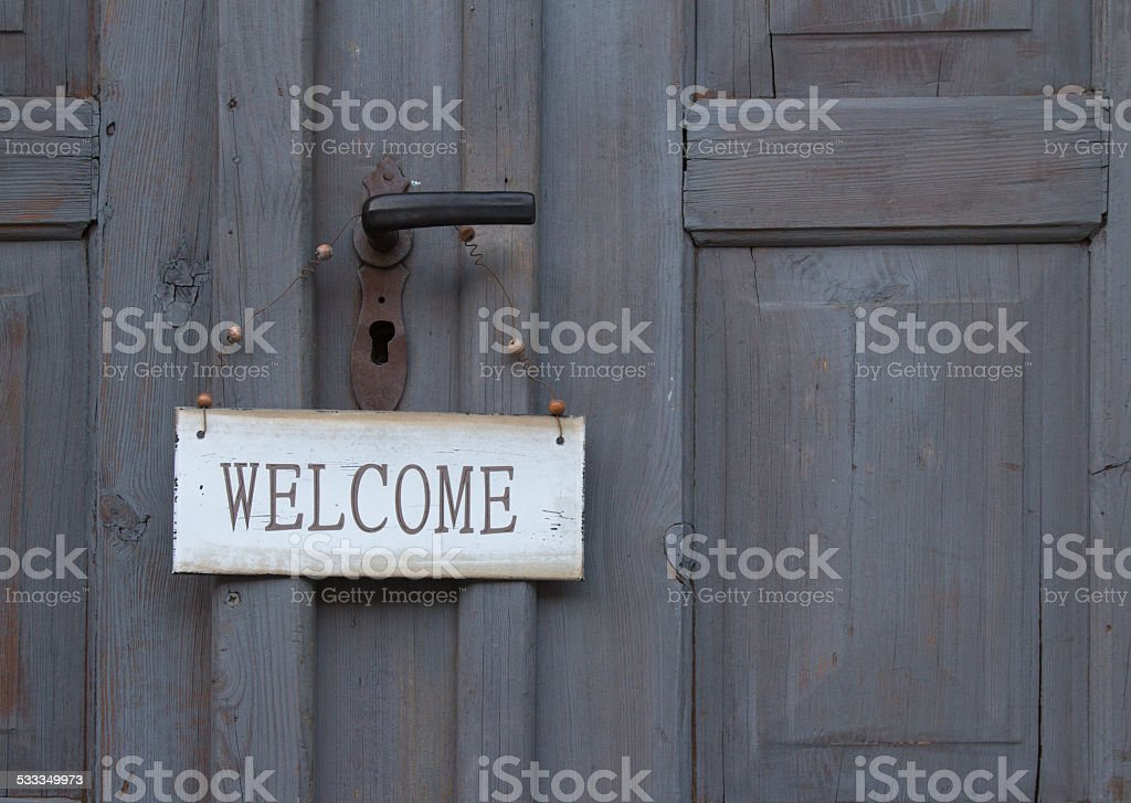 Welcome sign hanging on an old wooden door stock photo