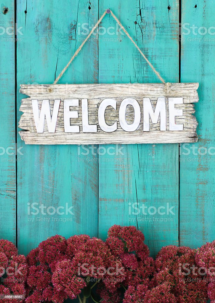 Welcome sign hanging on fence with stonecrop border stock photo
