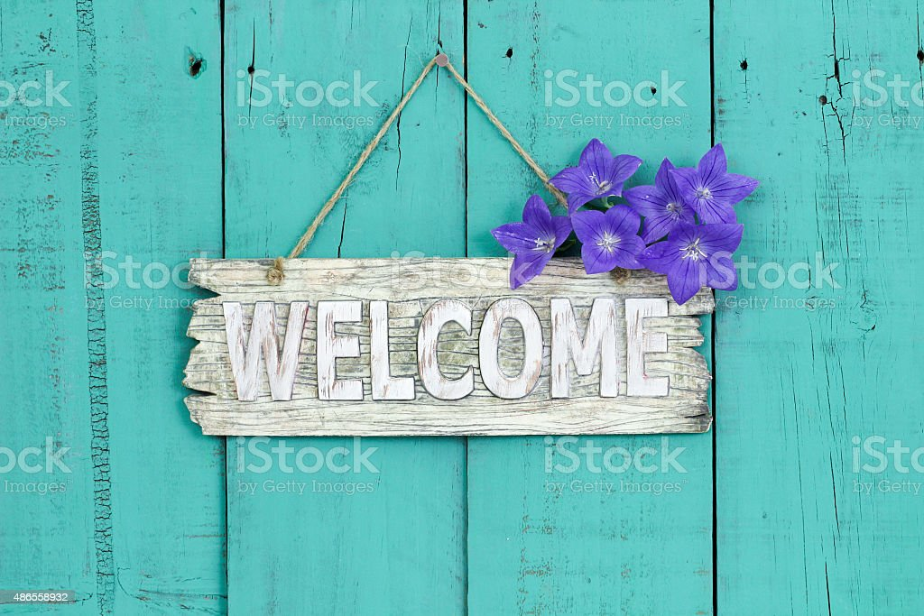Welcome sign with purple flowers stock photo