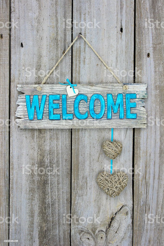 Welcome sign with rope hearts hanging on wood door stock photo