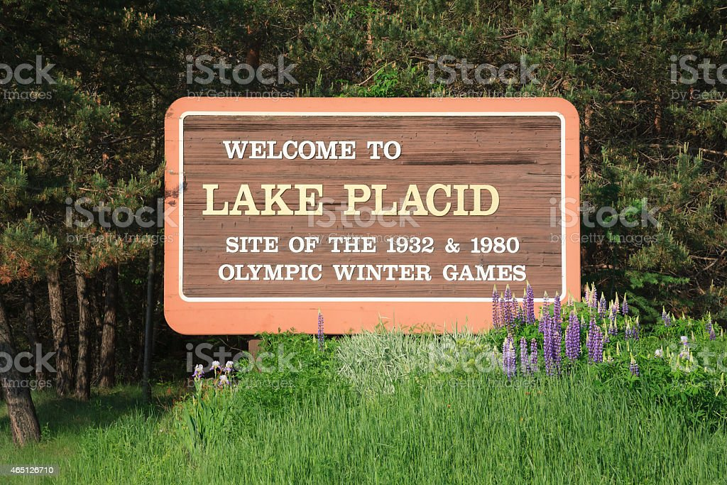 Welcome to Lake Placid highway road sign trees grass stock photo