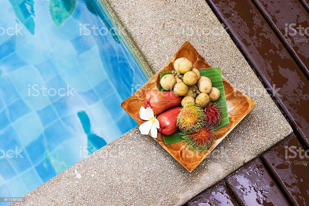 welcome tropical fruits on wooden tray near swimming pool stock photo