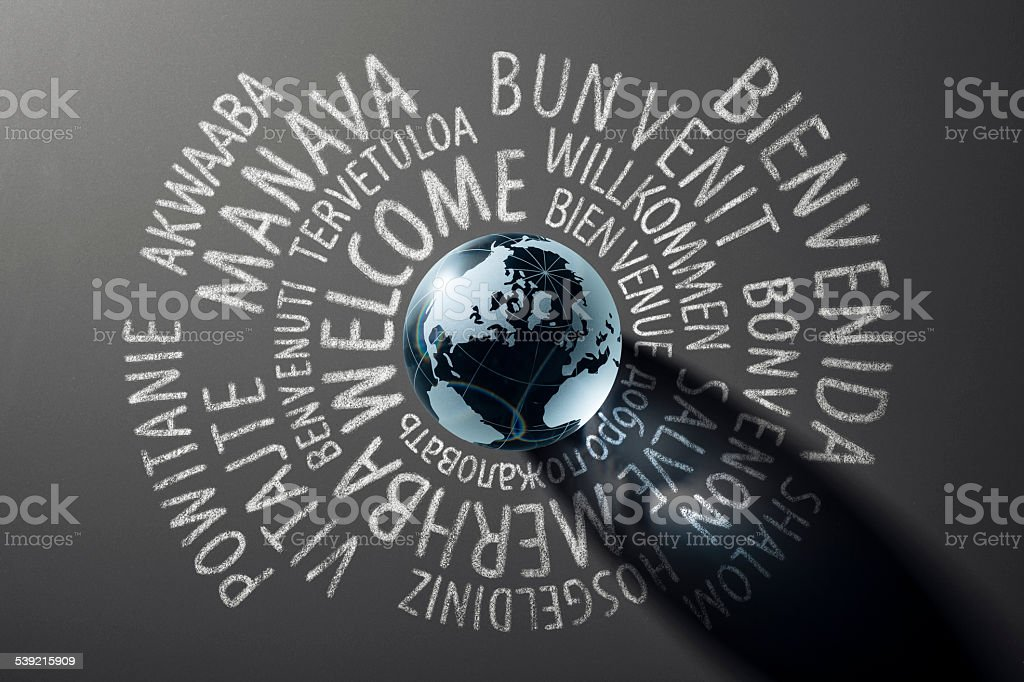 Welcome world globe with translations on blackboard - Backgrounds Cooporate stock photo