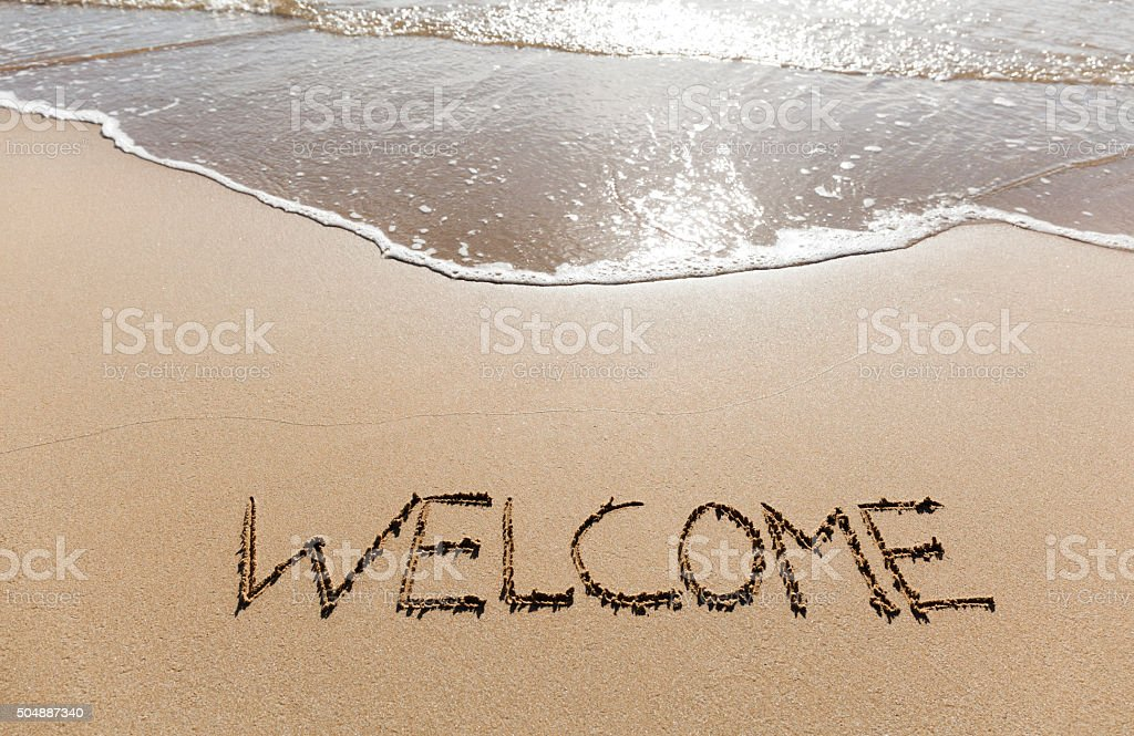 Welcome written in the sand on a beach. stock photo