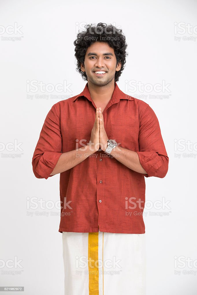 welcoming cheerful young man in traditional wear stock photo